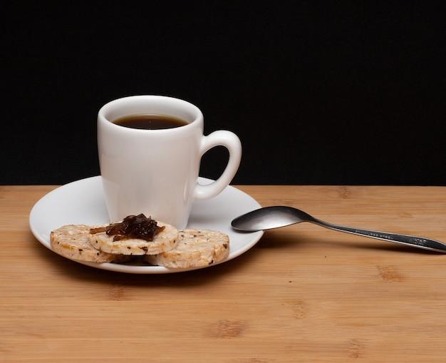 Tazza di caffè accanto a biscotti vegani di riso con gelatina sulla parte superiore e cucchiaio sotto il tavolo di legno