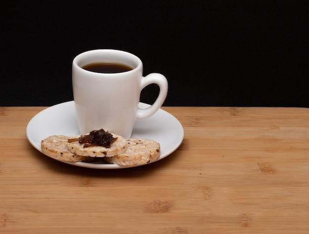 Tazza di caffè accanto a biscotti vegani di riso con una gelatina in cima sotto il tavolo di legno