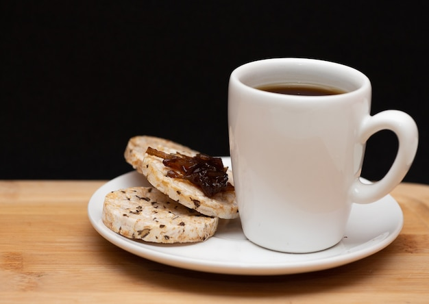 Una tazza di caffè accanto a biscotti vegani di riso con gelatina sulla parte superiore