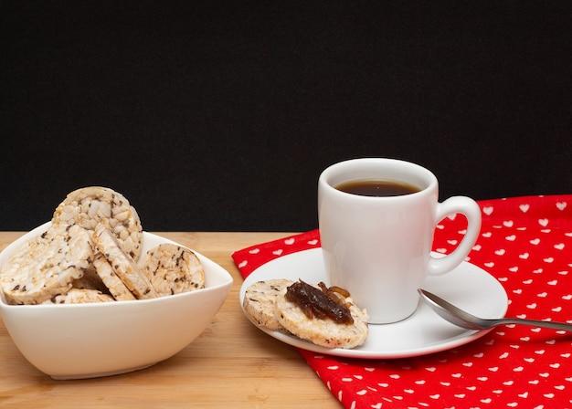 Una tazza di caffè accanto a un cucchiaio e una ciotola piena di biscotti vegani di riso con gelatina in cima