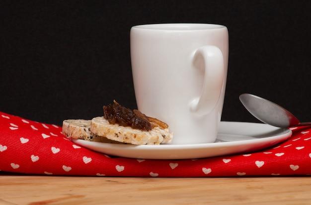 Una tazza di caffè accanto a un cucchiaio e un biscotto vegano di riso con una gelatina in cima