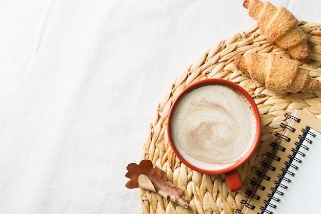 Tazza di caffè e pasticceria su sfondo bianco, umore autunnale