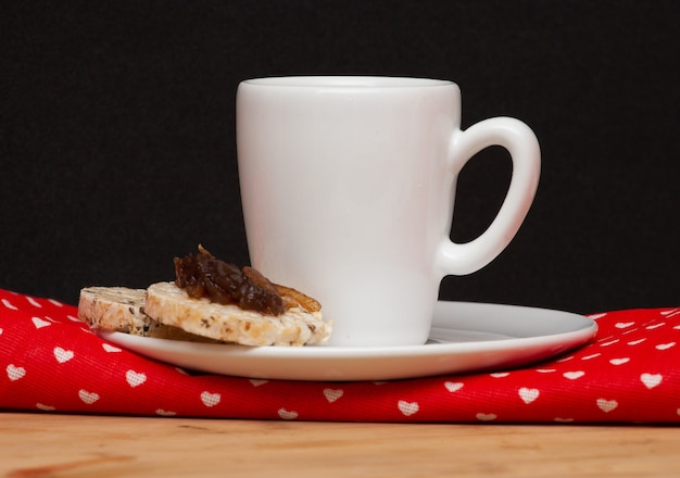 Una tazza di caffè e un biscotto vegano di riso con una gelatina sopra
