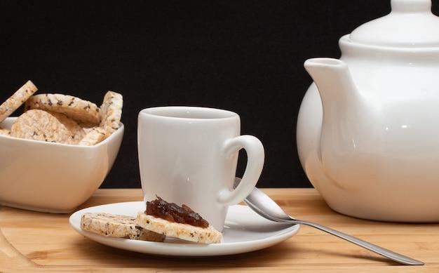 Una tazza di caffè circondata da una ciotola piena di biscotti di riso e una caffettiera