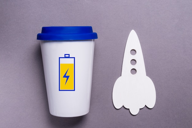 Tazza di caffè con batteria carica, concetto ad alta energia