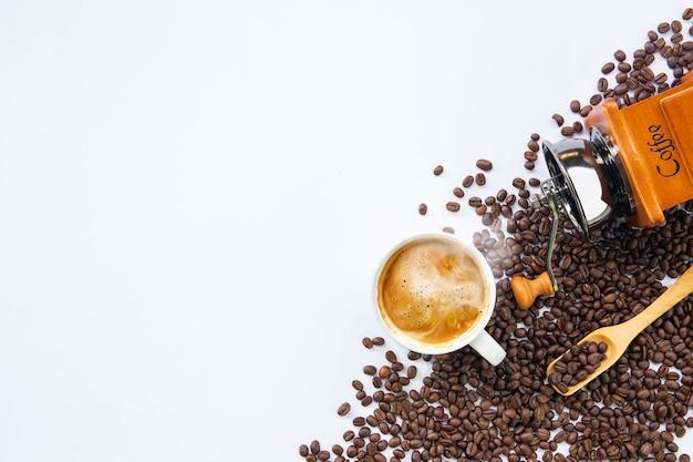 Tazza di caffè e fagioli sul fondo bianco della tavola. vista dall'alto