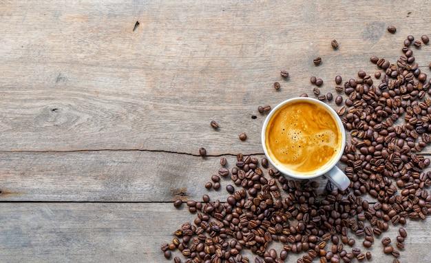 Tazza di caffè e fagioli sul pavimento di legno.