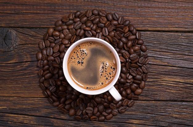 Tazza di caffè e fagioli disposti a forma di cerchio su sfondo di legno scuro, vista dall'alto