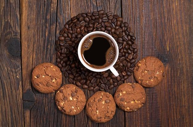 Tazza di caffè, fagioli a forma di cerchio e biscotti al cioccolato con noci su fondo di legno scuro, vista dall'alto