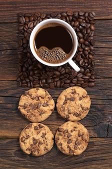 Tazza di caffè, fagioli a forma di quadrato e biscotti con cioccolato sul tavolo di legno scuro, vista dall'alto