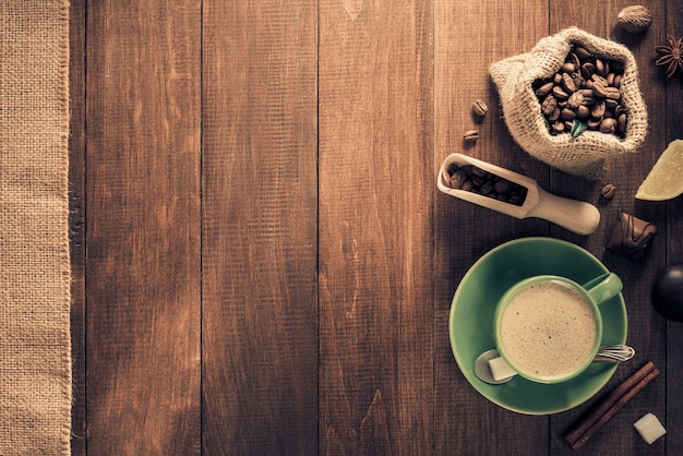 Tazza di caffè e fagioli su fondo di legno