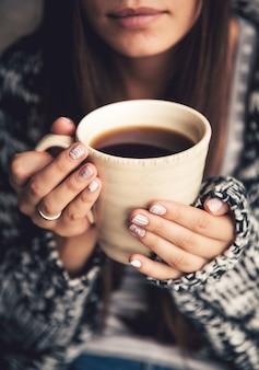 Una tazza di caffè in belle mani femminili e belle labbra