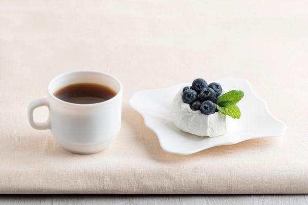 Tazza di caffè accanto al dessert ai frutti di bosco. torta e tè freschi della meringa ai mirtilli.