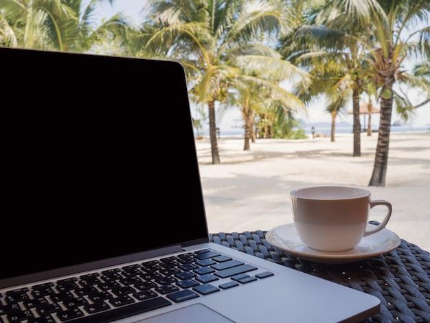Una tazza di caffè accanto al computer portatile con l'albero di cocco e lo sfondo della spiaggia di sabbia bianca con vista sul mare