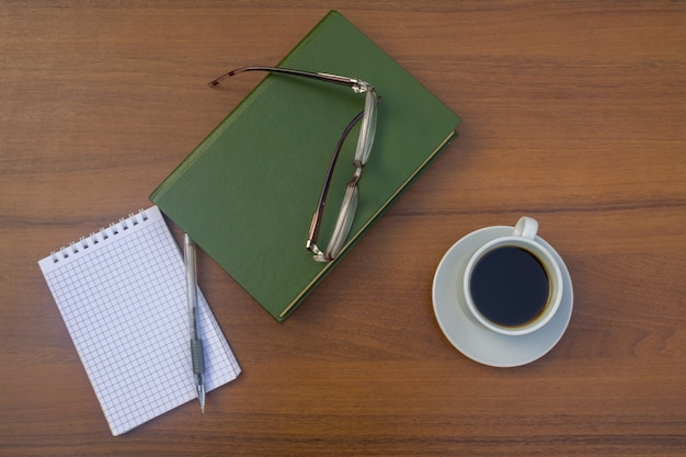 Tazza di caffè, libro, blocco note, penna e occhiali sulla scrivania in legno