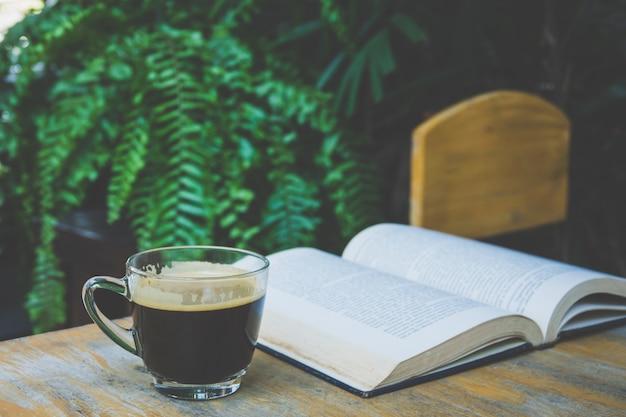 Tazza di caffè e un libro su un tavolo di legno