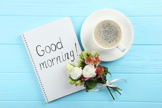 Una tazza di caffè un mazzo di fiori e un biglietto con le parole buongiorno