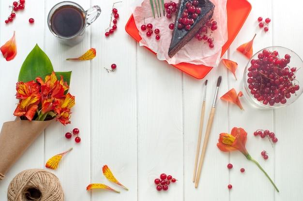 Tazza di caffè, torta e fiori su legno bianco