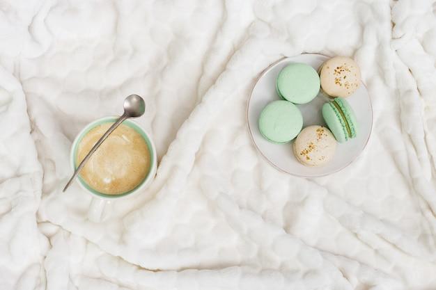 Cappuccino del caffè della tazza e maccheroni dolci saporiti sul fondo bianco del tessuto con lo spazio della copia. concetto di winter morning, tempo di relax. vista dall'alto.