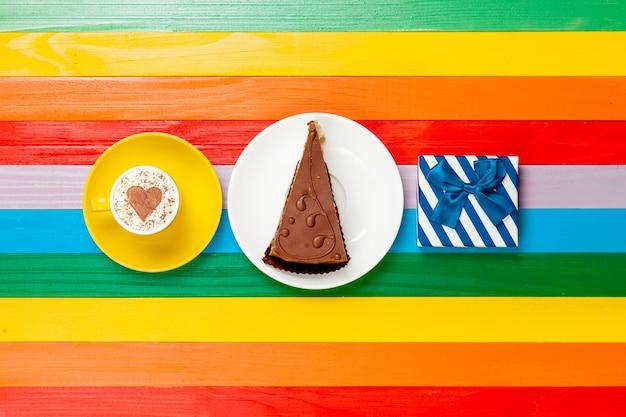 Tazza di caffè cappuccino con torta e confezione regalo su arcobaleno