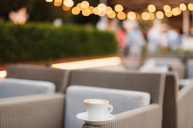 Una tazza di caffè su una sedia in un ristorante con sullo sfondo le luci della ghirlanda