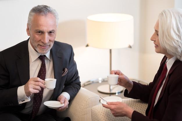 Tazza di caffè. allegro uomo d'affari invecchiato felice sorridente e seduto in ufficio mentre beve un caffè con il suo collega ed esprime felicità