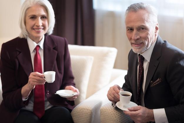 Tazza di caffè. donna di affari invecchiata felice allegra sorridente e seduta in ufficio mentre beve un caffè con il suo collega ed esprime felicità