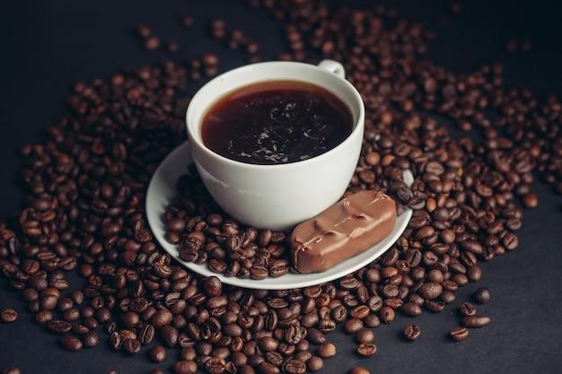 Una tazza di caffè e una barretta di cioccolato su una bevanda di varietà di fagioli arabica piattino.