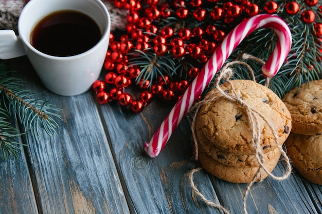 Tazza di caffè e biscotto con gocce di cioccolato mescolati con decorazioni festive per le vacanze invernali. spirito natalizio e concetto di svago. stringa di perline rosse su ramo di abete e bastoncino di zucchero.