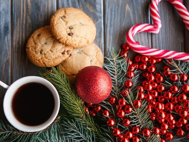 Tazza di caffè e biscotto con gocce di cioccolato circondati da festose decorazioni per le vacanze invernali. spirito natalizio e concetto di svago. corda di perline rosse palla ramo di abete e mix di bastoncini di zucchero.