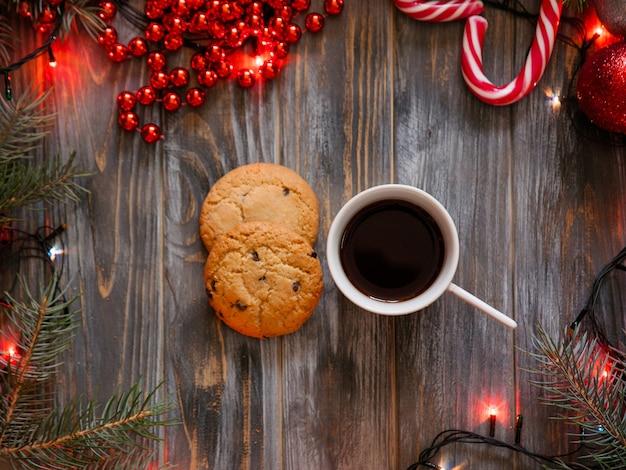 Tazza di caffè e un biscotto con gocce di cioccolato circondati da decorazioni festive per le vacanze invernali. spirito natalizio e concetto di svago.