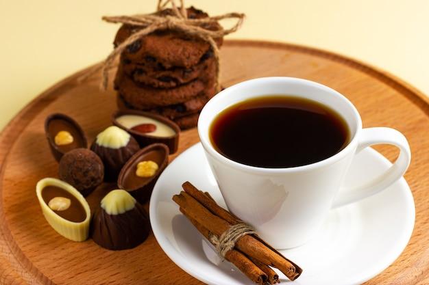 Tazza di caffè e cioccolatini su un vassoio in legno