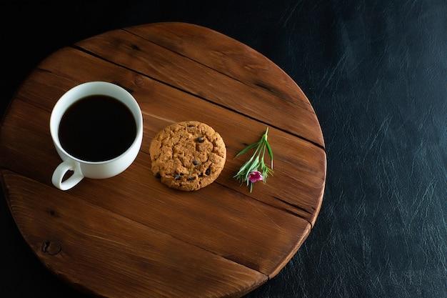 Tazza di caffè, biscotti e fiorellino rosa sul vassoio in legno
