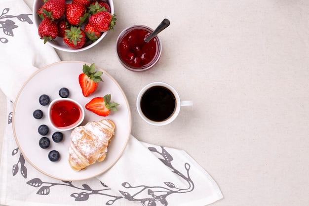 Tazza di caffè, croissant e marmellata di fragole mature e mirtilli su uno sfondo bianco piatto lay flat