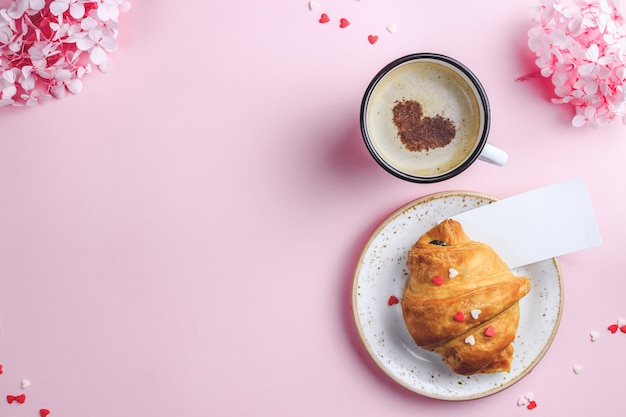 Tazza di caffè, cornetto su sfondo rosa con carta vuota