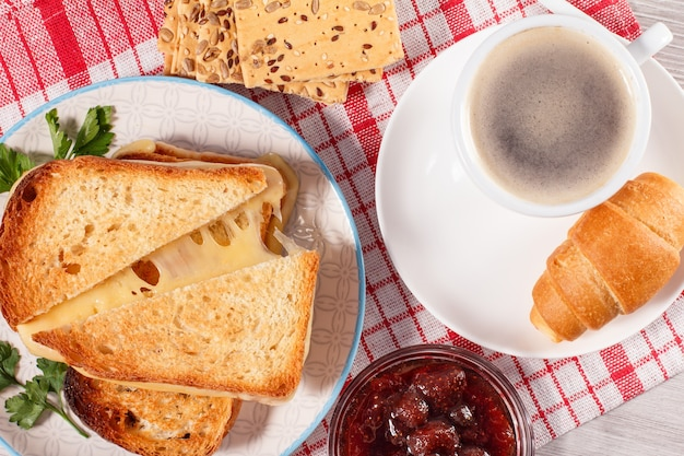 Tazza di caffè e croissant sul piattino ciotola di vetro con biscotti alla marmellata di fragole con cereali integrali