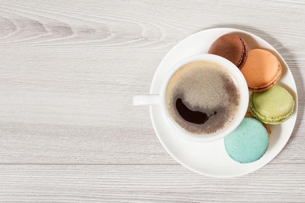 Tazza di caffè, deliziose torte di macarons di colore diverso su piatto di porcellana bianca con fondo di legno grigio. vista dall'alto con copia spazio