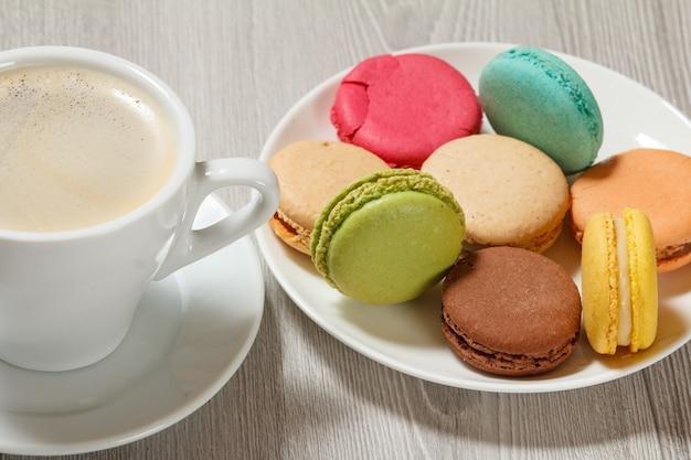 Tazza di caffè deliziose torte di macarons di colore diverso su un piatto di porcellana bianca