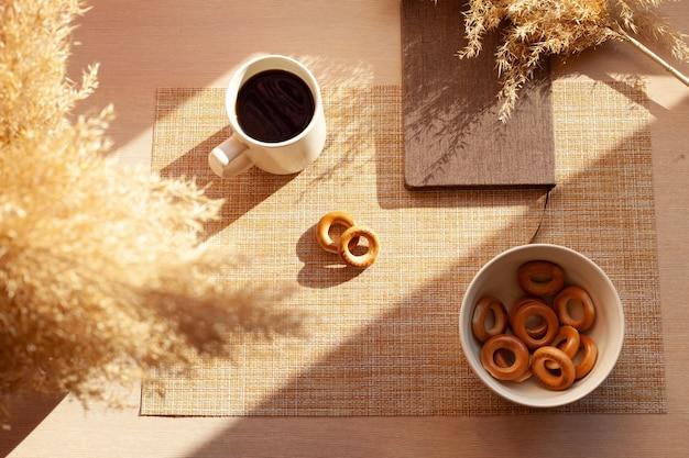 Una tazza di caffè, fiori secchi, barankis, blocco note sulla tavola di legno.