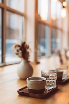 Tazza di caffè espresso e bicchiere d'acqua sulla tavola di legno