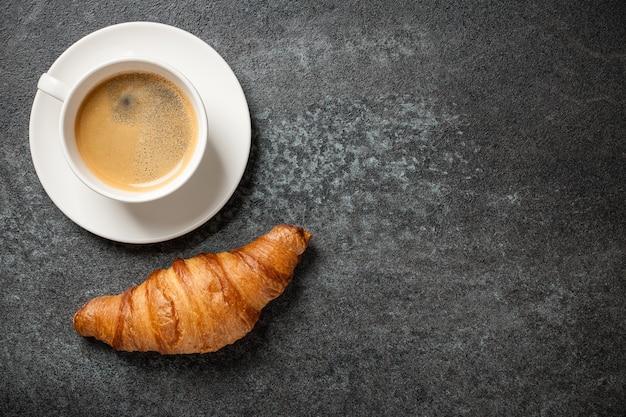 Tazza di caffè e croissant fresco sul tavolo nero