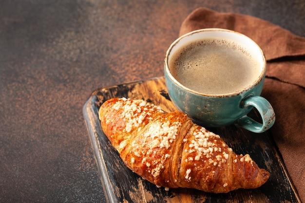 Tazza di caffè e croissant fresco