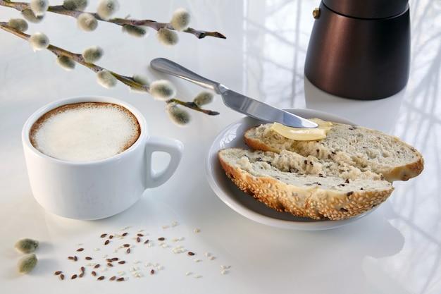 Tazza di caffè, caffettiera geyser e un panino di grano con burro su un tavolo bianco.