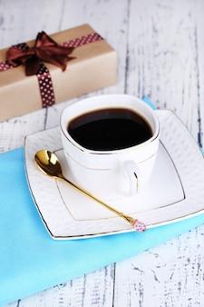 Tazza di caffè e regalo sul primo piano della tavola di legno