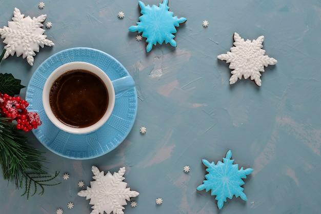 Tazza di caffè e biscotti di pan di zenzero a forma di fiocchi di neve su uno sfondo azzurro, vista dall'alto, orientamento orizzontale