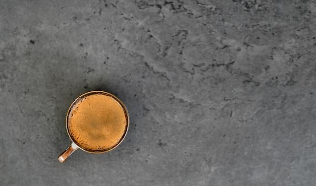 Tazza di caffè su uno sfondo di pietra grigia. vista dall'alto con copia spazio. ristretto forte o espresso con caffè schiumoso