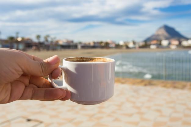 Tazza di caffè in mano sullo sfondo di una bellissima spiaggia.