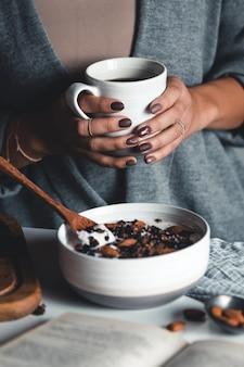 Tazza di caffè in mano. la ragazza sta facendo colazione. bella manicure. colazione salutare. ciotola di frullato