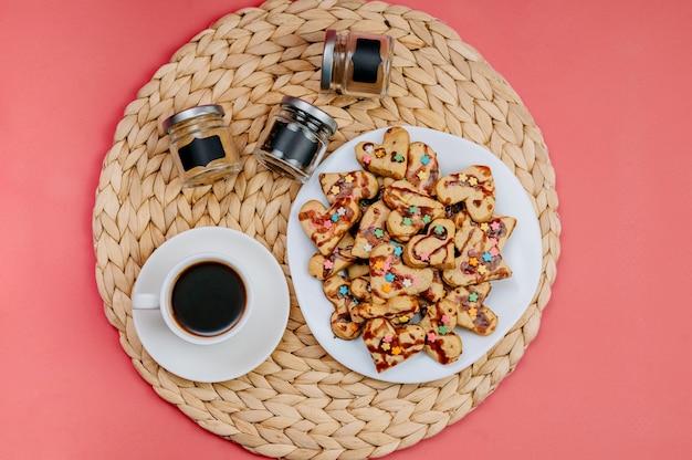 Tazza di caffè, biscotti fatti in casa e utensili da cucina su uno sfondo rosa.