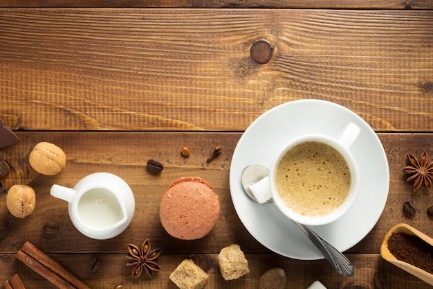 Tazza di caffè e ingredienti su fondo in legno, vista dall'alto